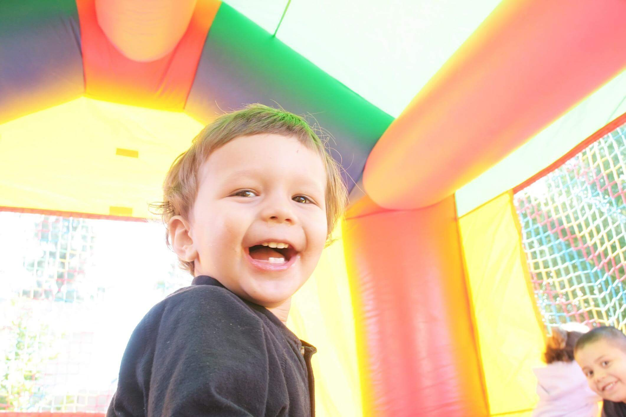 Two happy children in a red, yellow and green bouncy castle