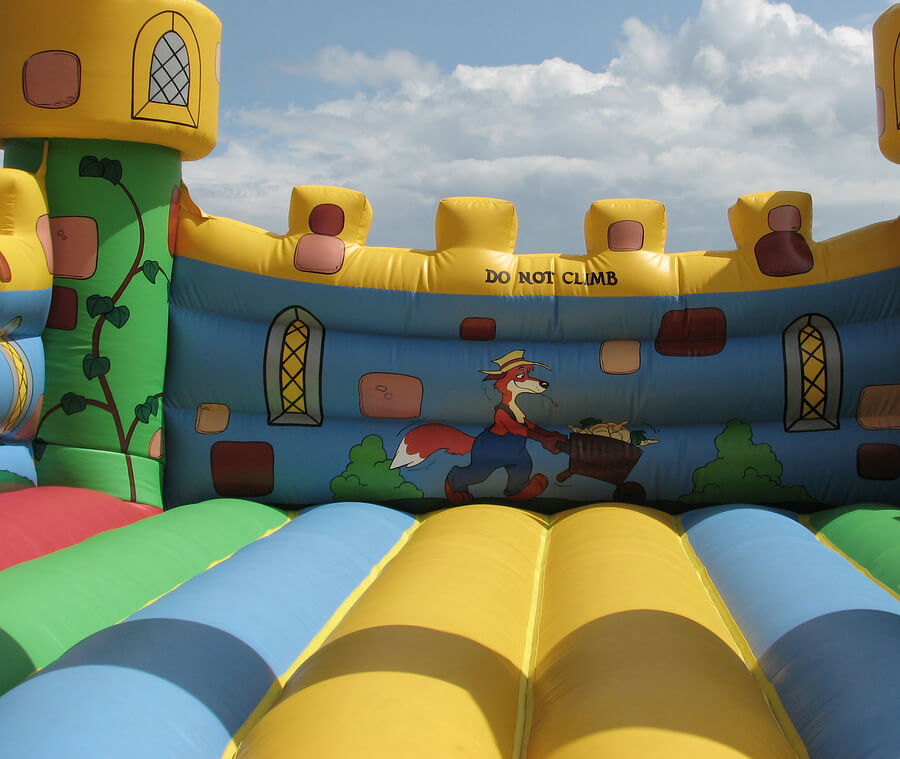 Bouncy or Jumping castle rental, decorated with a fox carying a wheelbarrow and yellow, green, blue and red colours