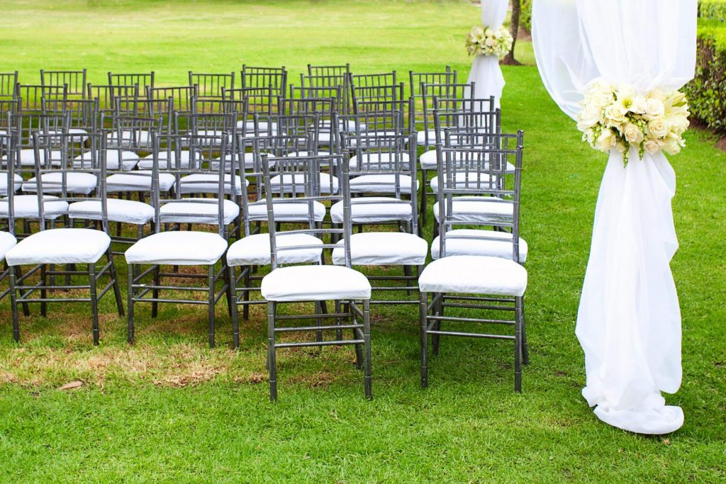 Rented white and silver chairs for a wedding party, surrounded with white drapes and yellow flowers on gras