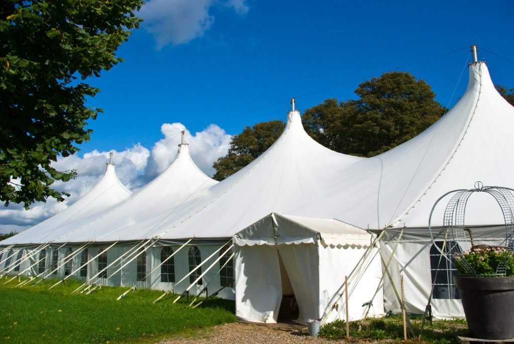 Rented large white Festival Tent secured to the ground and surrounded by trees and gras.