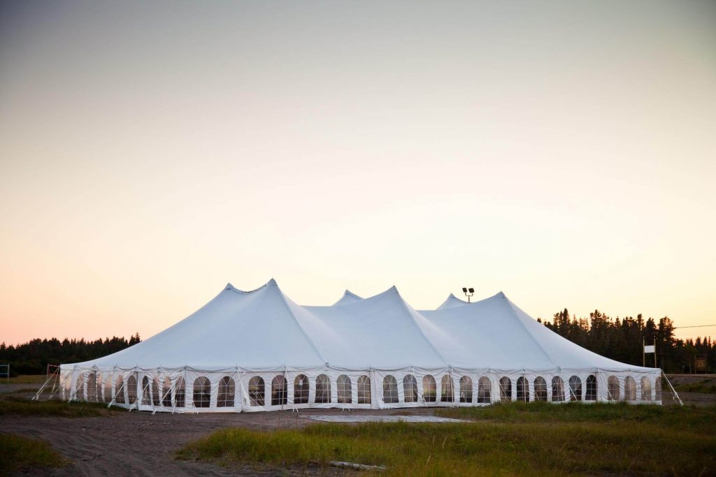 Very large closed white festival tent in evening light and surrounded by gras