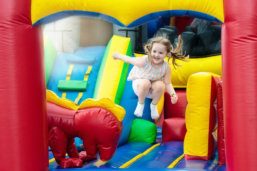 Happy little girl jumping on a red, yellow, green and blue bouncy castle rental