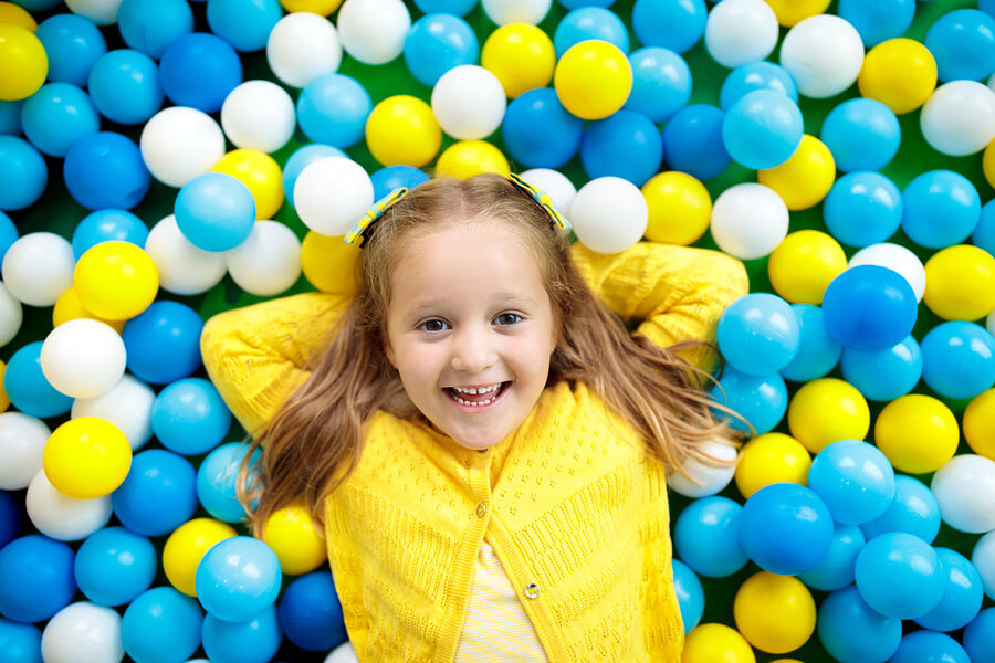 A little girl with dark blond hair dressed in yellow, lying in a ball pit with blue, yellow and white balls
