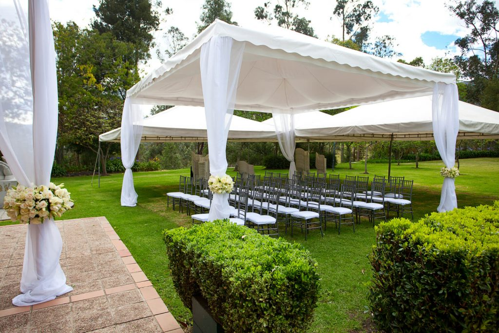 Lawn with surrounding trees and bushes, prepared for a wedding with white drapes, white and grey lawn chairs and small festival tents.