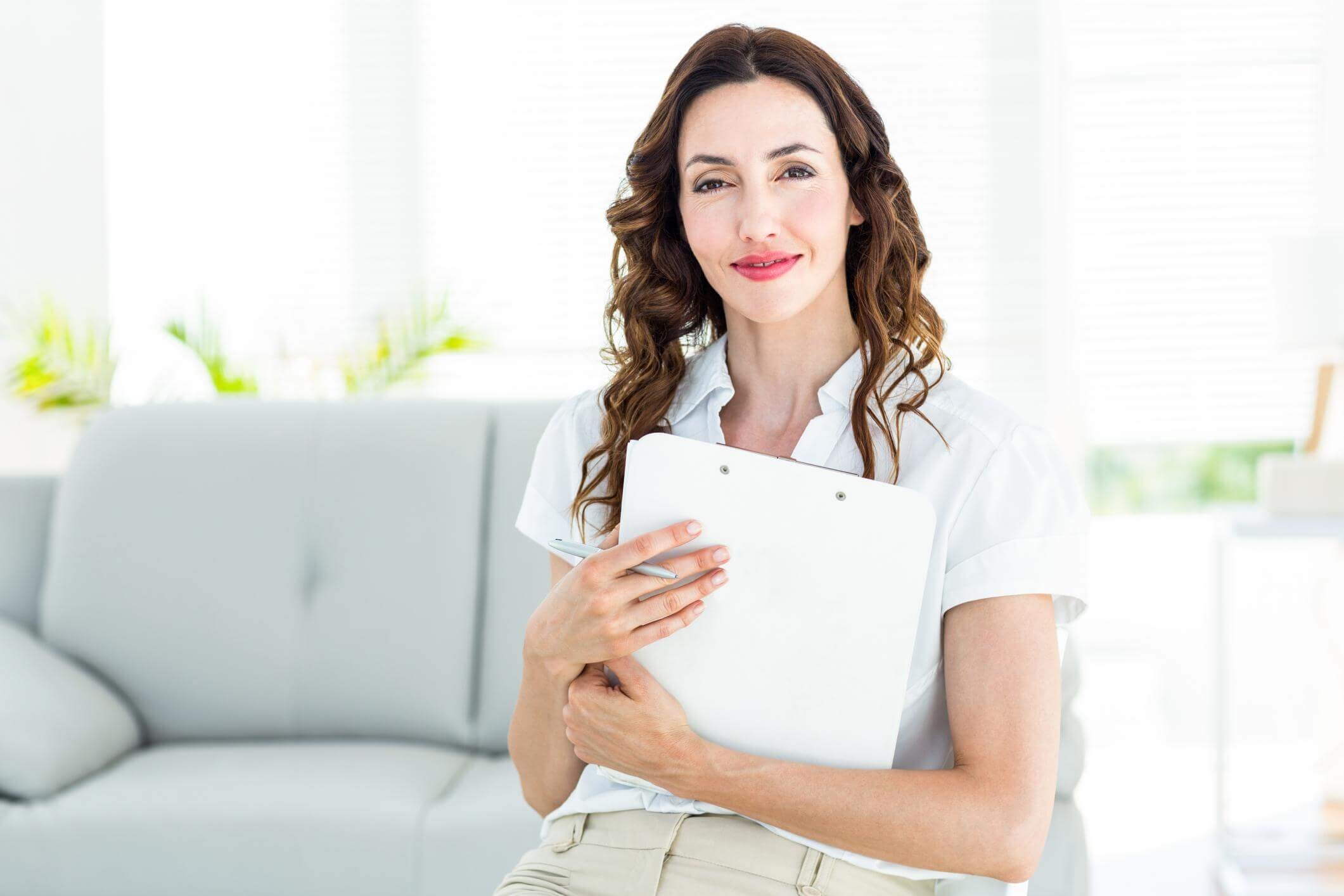 Brown haired woman holding a notepad and a pen in a bright environment and a couch on the background.