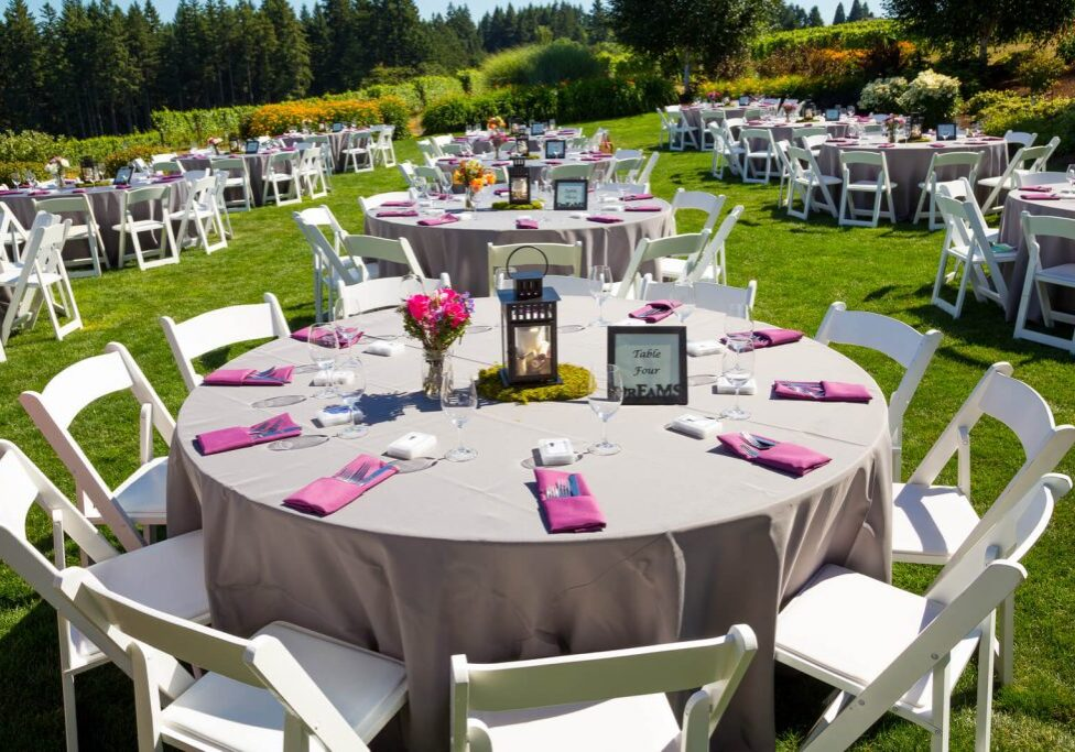 Rented tables and chairs at a wedding. All setup with cutlery, purple and grey finishes on a green lawn surrounded by nature